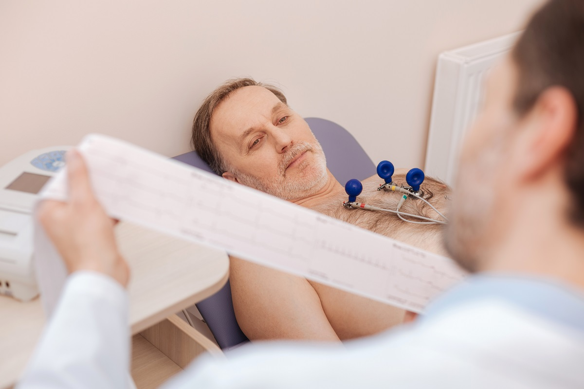 Cardiologist performing EKG on male patient